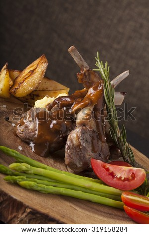 Rack of lamb steak, Rack of lamb steak cut in pieces decorate and seasoning with vegetable and herbs and red wine serve on chopping wood block