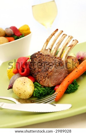 Rack of lamb with colorful roast vegetables, and a glass of wine.
