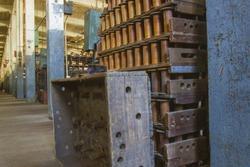 Rack of wooden bobbins on floor of turn of the century silk throwing factory.