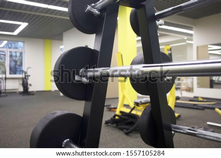 rack with a set of barbells of different weights in the gym, the concept of sports and exercise