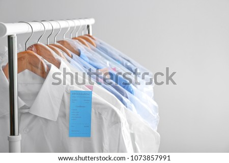 Rack with clean clothes on hangers after dry-cleaning against light background
