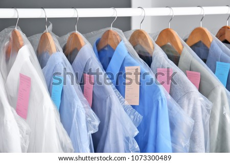 Rack with clean clothes on hangers after dry-cleaning indoors #1073300489