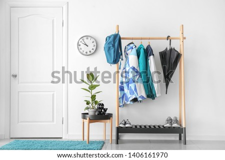 Rack with clothes in stylish interior of hall Zdjęcia stock ©