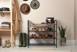 Rack with different shoes near beige wall in room