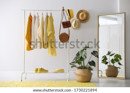 Rack with stylish women's clothes and mirror indoors. Interior design Photo stock ©