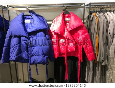 Rack with warm coats of colors and black clothes in clothes shop.