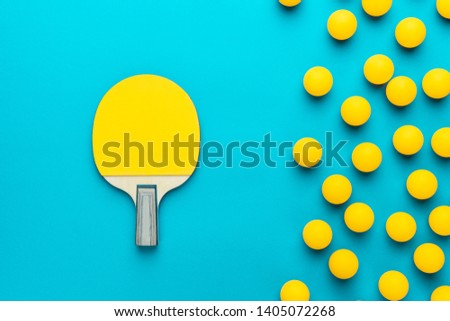racket and many balls for table tennis on turquoise blue background. flat lay image of many table tennis balls and paddle. minimalist photo of yellow ping-pong equipment