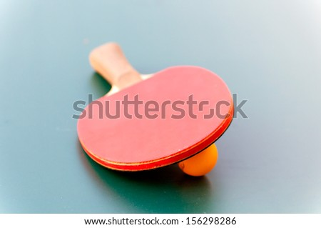 racket for tennis and ball lying on a green table