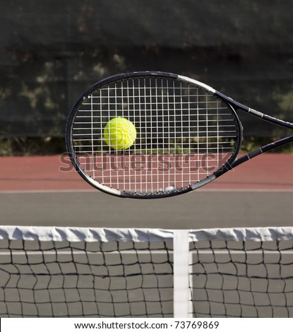 Racket with tennis ball on court hit