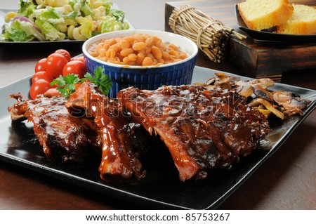 Racks of barbecue ribs drenched in sauce with salad and cornbread