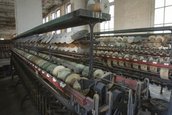 Racks of empty thread spools inside turn of the century silk throwing factory.