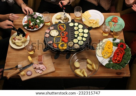 Raclette grill party friends eating grilled vegetable drinking beer on vintage wooden desk