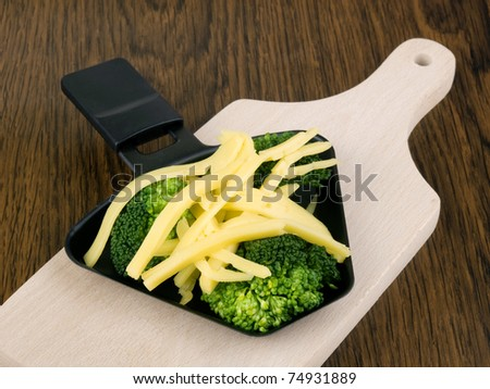 Raclette pan with cheese and broccoli on chopping board