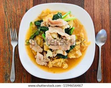 Rad Na,Thai food, Thai noodles topped with pork and kale,fork and spoon on wood table  #1194656467