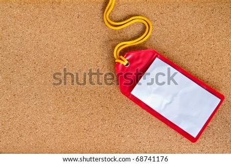 Rad plastic luggage tag isolated on cork board background