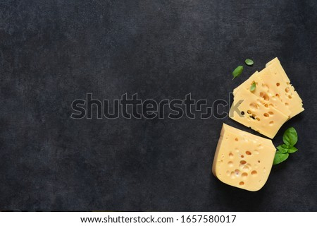 Radamer cheese on a black concrete background. View from above.