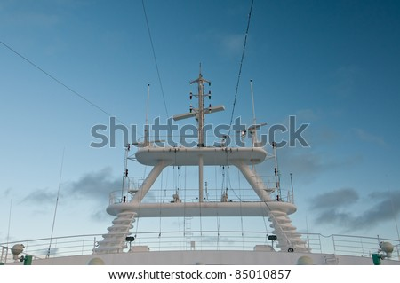 Radar and communications equipment on cruise ship with blue sky.
