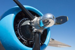 Radial engine on a vintage aircraft with propeller and a polished spinner against a blue sky