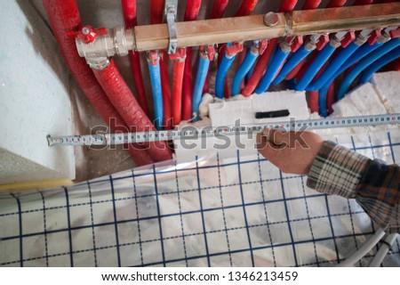 Radiant Floor Heating Installation Heating System. Man install underfloor water heating floor construction. Floor heating installation. #1346213459