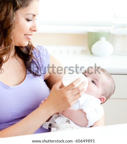 Radiant mother feeding her adorable son in the kitchen at home