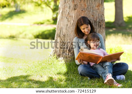 Radiant mother with her daughter looking at their album photo