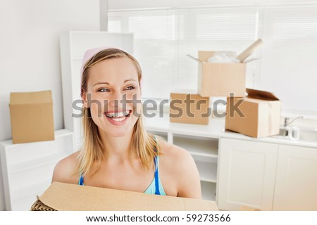 Radiant woman holding boxes after moving