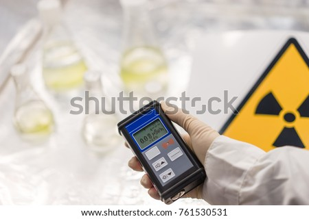 Radiation supervisor in glove with geiger counter checks the level of radiation in the radioactive zone