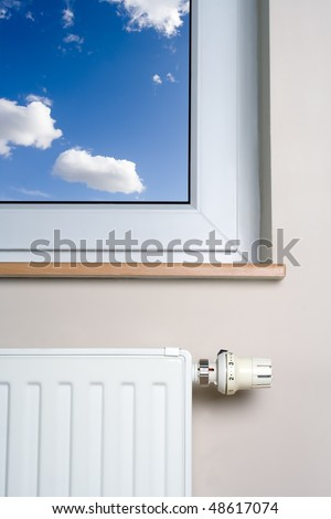 Radiator and blue sky in home interior, heater and thermostat