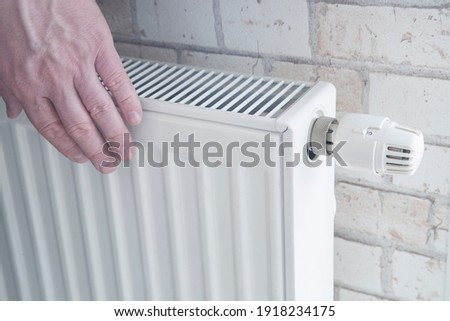 Radiator for home heating. Water heating. Hands of a man on the radiator.