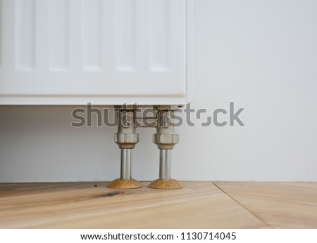 Radiator pipe covers sleeves. Install radiator for heating system with hiding pipes in the wooden floor. Radiator pipe sleeves.