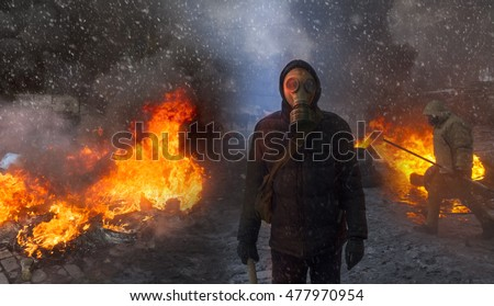 Radical Protestant in the mask represents the protesters against the authorities among the burning of the capital of the European quarter. Burning rubber tires wheel of fire smoke soot street fighting