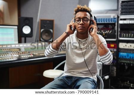 Radio deejay in headphones listening to soundtracks that he going to broadcast