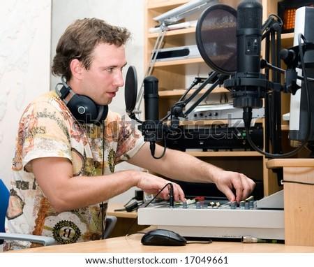 Radio DJ.  Young man with microphone and big headphone.
