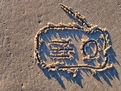 Radio receiver symbol drawn in sand of a sea beach during sunset.