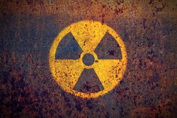 Radioactive (ionizing radiation) round yellow and black danger symbol painted on a massive rusty metal wall with dark rustic grunge texture background. Nuclear, radioactive alert concept.