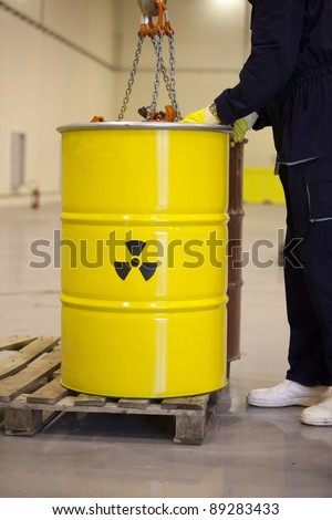 Worker handling toxic waste barrel