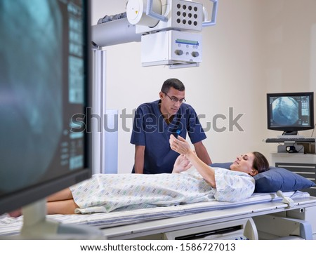 Radiographer With Female Patient In Hospital X Ray Department