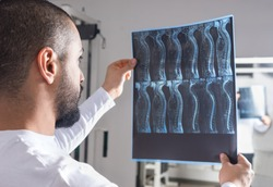 Radiologist analysing X-ray image with human spine in consulting room