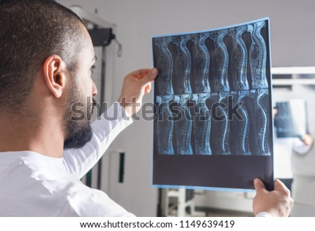 Radiologist analysing X-ray image with human spine in consulting room #1149639419