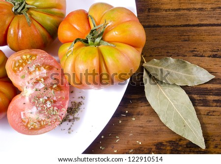 Raff tomatoes on wood table and oregano