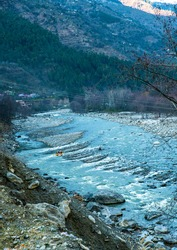 Rafting : boat moving on quiet  river section-river Beas in Himachal Pradesh.  serviceman control boat himself , tourists making selfieand enjoy . Unrecognizable persons.