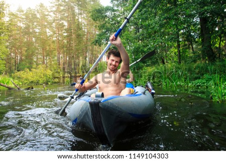 Rafting in a canoe by the river. Young guys with oars in a boat sail on the river in the summer. Active leisure rafting on the river. Young athletic man in a kayak with an oar rowing on the water #1149104303