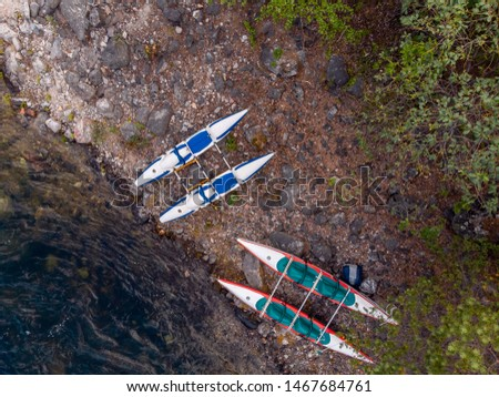 Rafting kayaks on bank of mountain river with rocky shore. Aerial top view.