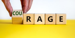 Rage or courage symbol. Businessman turns a cube and changes the word 'rage' to 'courage'. Beautiful yellow table, white background. Copy space. Business and rage or courage concept.