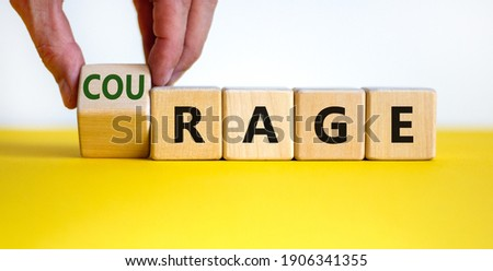 Rage or courage symbol. Businessman turns a cube and changes the word 'rage' to 'courage'. Beautiful yellow table, white background. Copy space. Business and rage or courage concept. Сток-фото ©