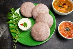Ragi Idly, finger millet Idli, Sambar, coconut chutney healthy home made breakfast dish Kerala, Karnataka, India. steam cooked finger millet batter. Top view South Indian food dark black background.