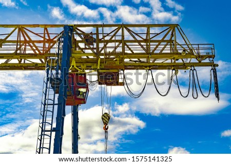 Rail crane for unloading railway cars in  industrial zone of city. Against background of blue sky and white beautiful clouds. View from below. #1575141325