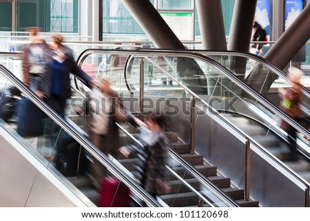 rail station with people in motion blur on the escalator