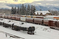 rail yard in winter with trains, depot, and mountains in background Whitefish, Montana