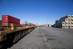 Rail yard with containers loaded onto train with flat deck trucks